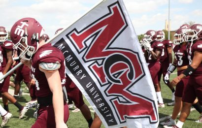 football players carrying the McMurry Flag